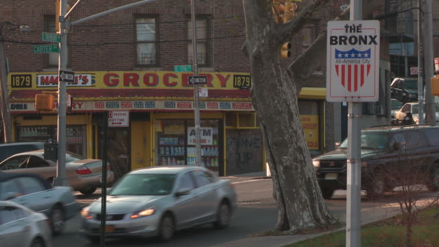 """The Bronx All American City"" sign with traffic passing on east tremont avenue near carter avenue and east 176 street in front of macori's grocery late in the day"