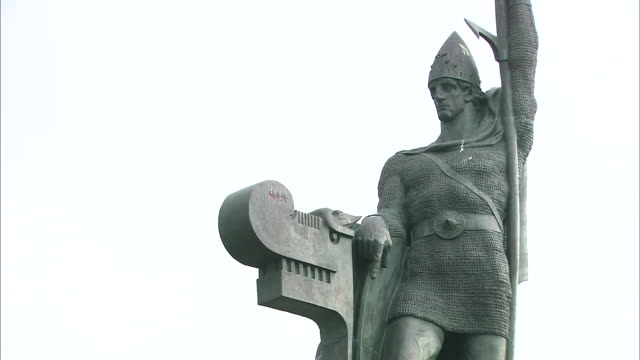 the bronze statue of an early icelandic settler contrasts against a bright white sky. - male likeness stock videos & royalty-free footage