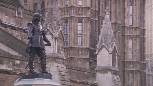 the bronze statue of oliver cromwell stands among the spires of parliament. - britisches parlament stock-videos und b-roll-filmmaterial