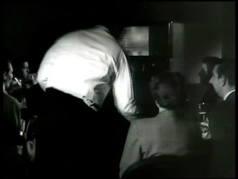 the brook restaurant window w/ 'television' 'boxing tonight' neon sign in window. int darkened bar w/ people sitting watching television tv boxing... - 1948年点の映像素材/bロール