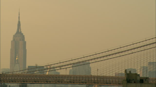 the brooklyn bridge and empire state building stand out against a peach colored sky at twilight. - air pollution stock videos & royalty-free footage
