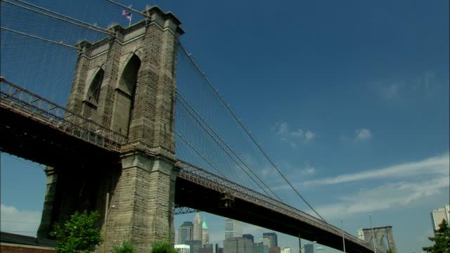 the brooklyn bridge spans the east river in new york city. - ブルックリン橋点の映像素材/bロール
