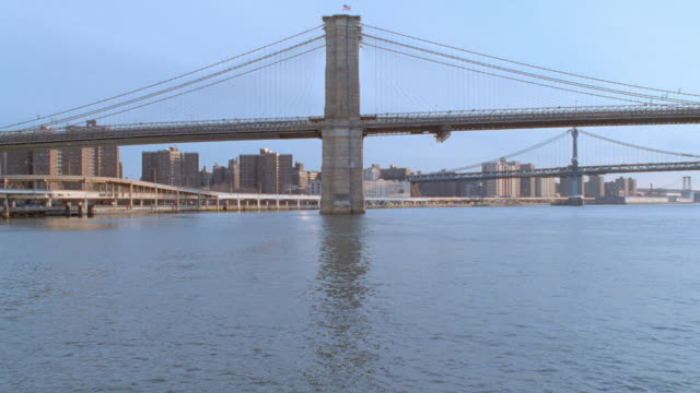 the brooklyn bridge spans the east river near new york city. - ponte video stock e b–roll