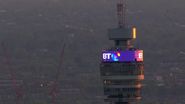 vídeos de stock e filmes b-roll de the bt logo shines near the top of bt tower in the fitzrovia neighborhood of london, england. - bt tower londres