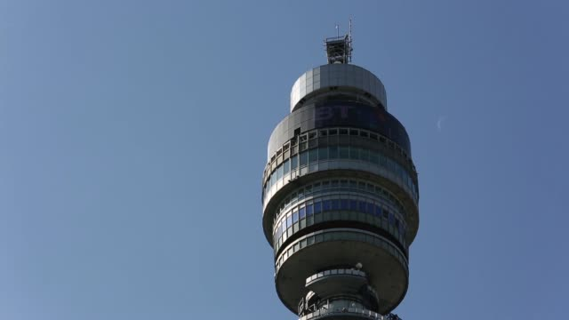 vídeos de stock e filmes b-roll de the bt tower british telecom tower sits in central london tilt down tilt up top of the bt tower to logo communications equipment low angle view of... - bt tower londres