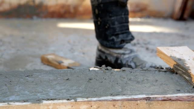 Der Baumeister vertreibt den Beton entlang der hölzernen Schalung.