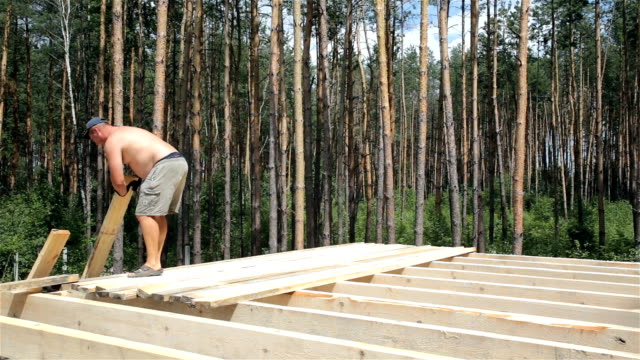 The builder lifts the rafters onto the roof and stacks them on the beams.