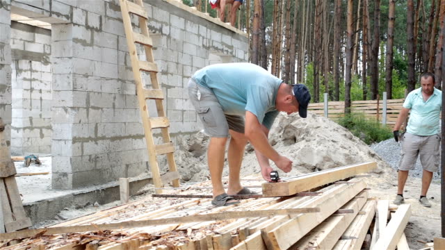 the builder measures the length of the wooden beam. - roof beam stock videos & royalty-free footage