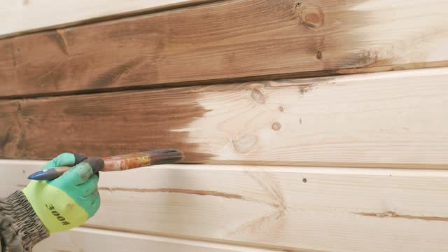 the builder paints the wall of the house. close-up. - wood stain stock videos & royalty-free footage