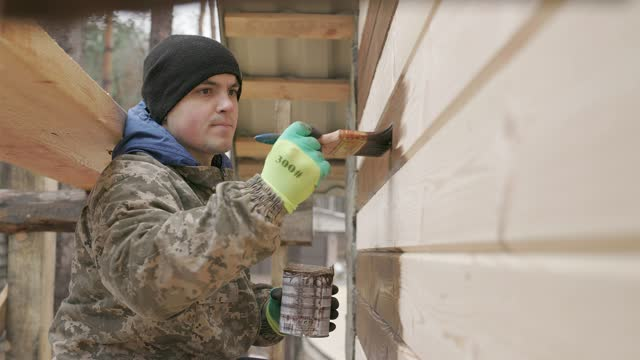 the builder paints the wall of the house. - wood stain stock videos & royalty-free footage