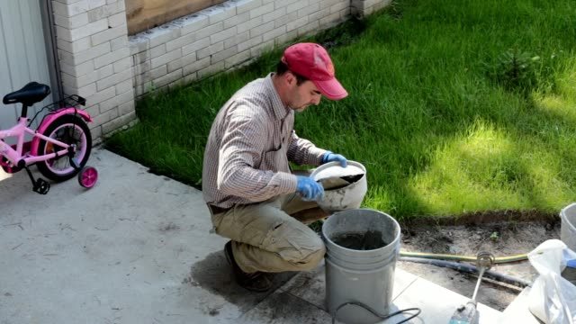 the builder puts the mortar in the sprayer. - plaster stock videos and b-roll footage
