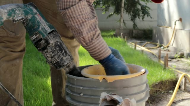 the builder sifts the cement to prepare a mortar. - drill stock videos & royalty-free footage