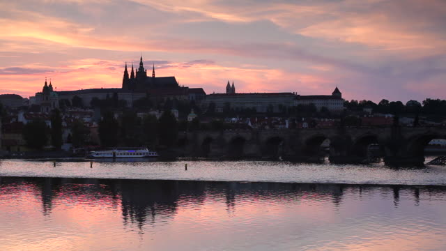 The buildings in the Castle District of Prague reflect on the surface of the Vltava River.