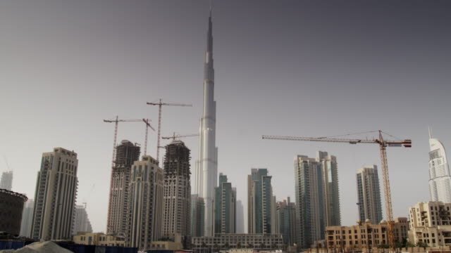 the burj khalifa, tallest building in the world, surrounded by smaller skyscrapers and cranes in dubai, united arab emirates. - クレーン点の映像素材/bロール
