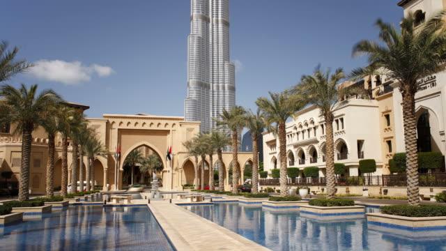 the burj khalifa towers over a courtyard in dubai. - 顕花植物点の映像素材/bロール