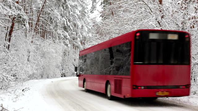 vidéos et rushes de le bus se déplace le long de la route enneigée à travers la forêt. - car