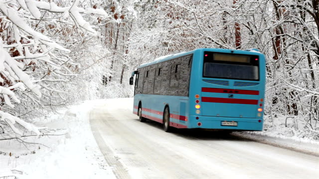the bus moves along the snowy road through the forest. - tour bus stock videos and b-roll footage