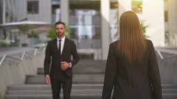The businessman and businesswoman meet near the business office