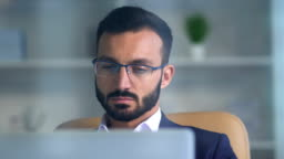 The businessman in glasses working in the office