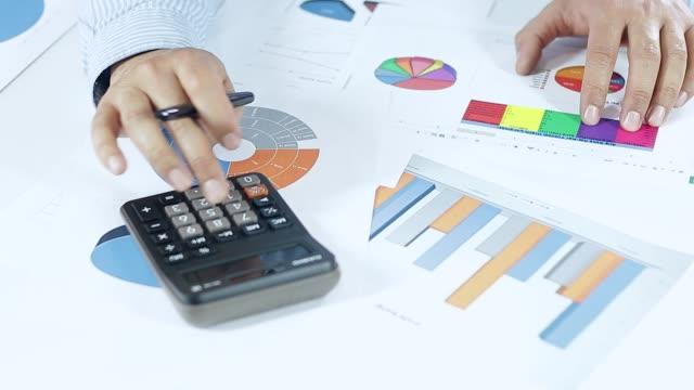 vídeos y material grabado en eventos de stock de el empresario está haciendo cuenta de datos con la calculadora - hoja de cálculo
