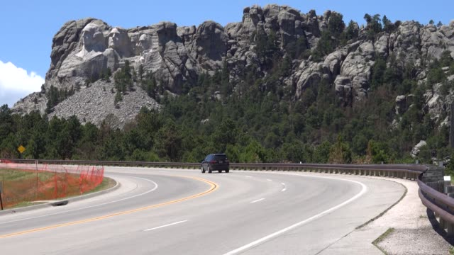 the busts of us presidents george washington thomas jefferson theodore roosevelt and abraham lincoln tower over the black hills at mount rushmore... - thomas jefferson stock videos & royalty-free footage
