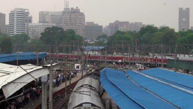 The busy New Delhi Railways Station (Code NDLS) with passengers and trains and the city skyline