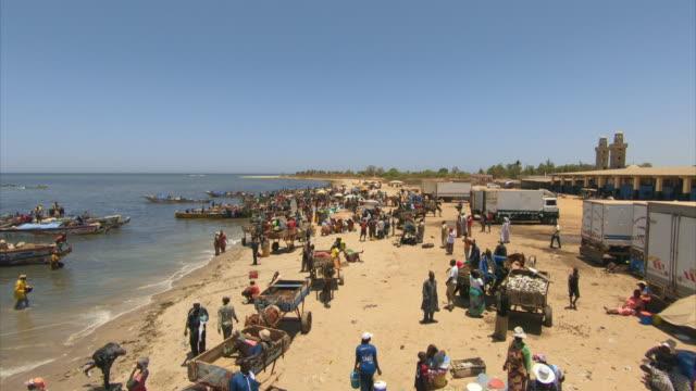 the busy shoreline of a senegalese fishing village - セネガル点の映像素材/bロール