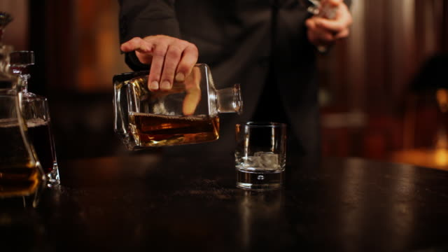The butler fills whiskey glass, having a closer look