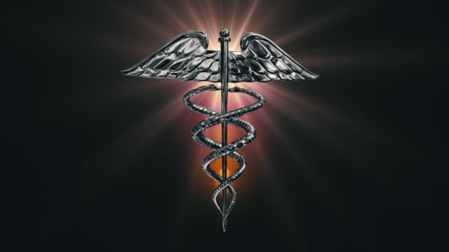 the caduceus medical symbol rotating on a golden lens flare (loop). - caduceus stock videos and b-roll footage