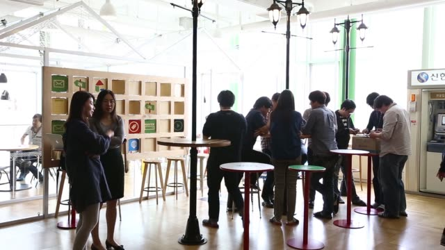 WS the cafeteria area at the Naver Corp headquarters MWS employees queue at the cashier WS employees gather at high tables in the cafeteria area MWS...