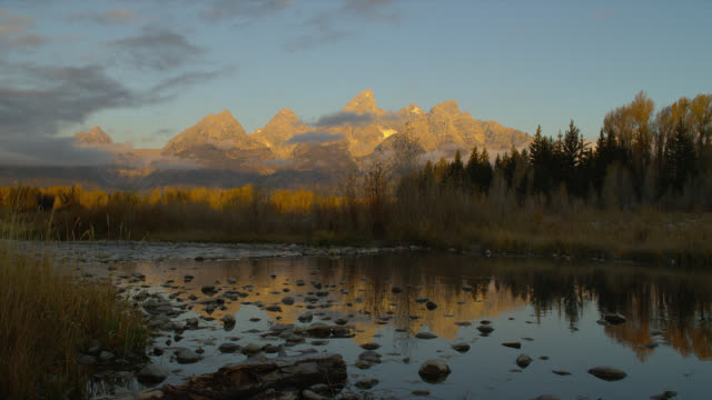 the calm snake river reflects wooded schwabacher's landing and the grand teton mountains at sunrise. - snake river stock videos and b-roll footage
