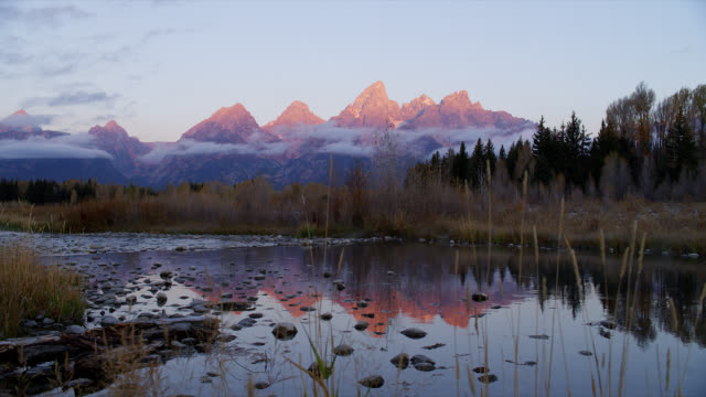 The calm water of the Snake River reflects the Tetons at golden hour.