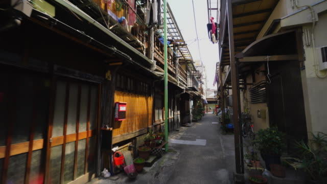 the camera captures the narrow alleyway in tsukishima downtown tokyo.there are japanese traditional nagaya style houses along the both side of alleyway. - 路地点の映像素材/bロール