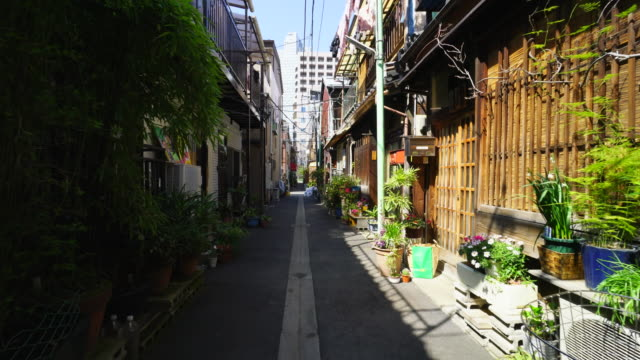 The camera captures the narrow alleyway in Tsukishima Downtown Tokyo.There are Japanese traditional Nagaya style houses along the both side of alleyway.