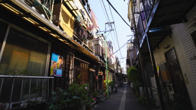the camera captures the narrow alleyway in tsukishima downtown tokyo.there are japanese traditional nagaya style balconies along the both side of alleyway, which are use for drying the laundry. - 路地点の映像素材/bロール
