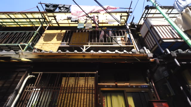 the camera captures the narrow alleyway in tsukishima downtown tokyo.there are japanese traditional nagaya style balconies, which are use for drying the laundry. - tradition stock videos & royalty-free footage