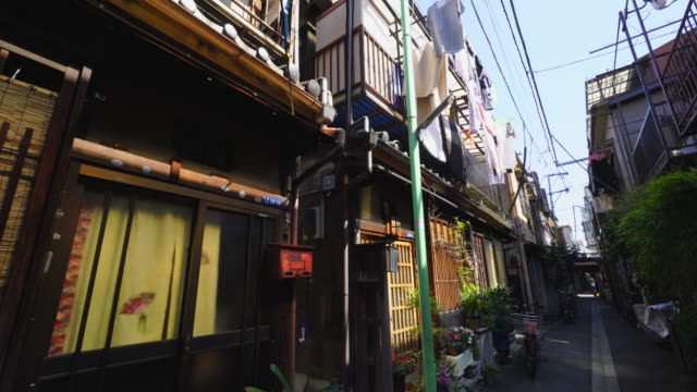 the camera captures the narrow alleyway in tsukishima downtown tokyo.there are japanese traditional nagaya style balconies along the both side of alleyway, which are use for drying the laundry. - shitamachi stock videos and b-roll footage