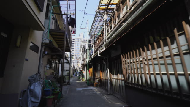 the camera captures the narrow alleyway in tsukishima downtown tokyo.there are japanese traditional nagaya style houses along the both side of alleyway. - alley stock videos & royalty-free footage