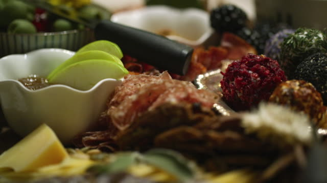 the camera focuses around an up-close shot of an appetizer charcuterie meat/cheeseboard with apple slices, garnishes, prosciutto, cheeses, a chocolate log, and blackberries at an indoor celebration/party - cheese ball stock videos and b-roll footage