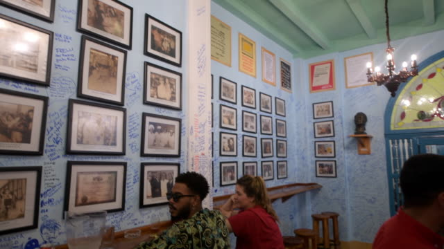 the camera goes from the old photos of famous personalities to the door of the restaurant inside of the newly opened restaurant and bar 'la bodeguita... - food bar stock videos and b-roll footage