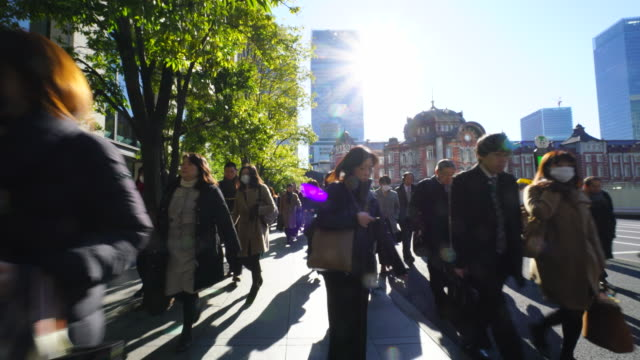 tl the camera goes through against the morning commute crowd.commuters go to marunouchi business district from tokyo station. - 保護マスク点の映像素材/bロール