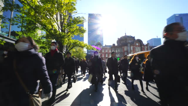 the camera goes through against the morning commute crowd.commuters go to marunouchi business district from tokyo station. - 保護マスク点の映像素材/bロール