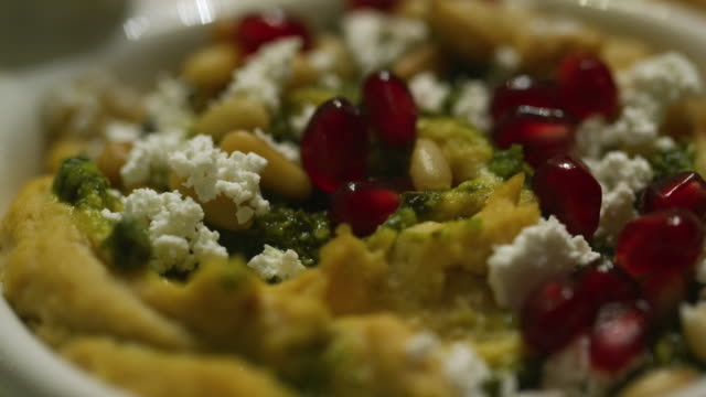 the camera pans an up-close shot of a hummus appetizer with feta cheese, pine nuts, spinach, and pomegranate arils (seeds) at an indoor celebration/party - greek food stock videos & royalty-free footage