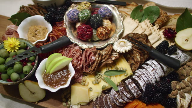 The Camera Pans Around an Appetizer Charcuterie Meat/Cheeseboard with Various Fruit, Sauces, and Garnishes on a Table at an Indoor Celebration/Party