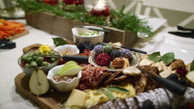 the camera pans around an appetizer charcuterie meat/cheeseboard with various fruit, sauces, and garnishes on a table at an indoor christmas celebration/party - cheese ball stock videos and b-roll footage