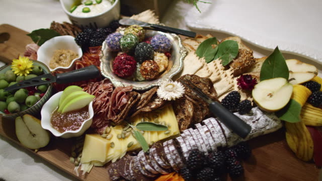 the camera pans around an appetizer charcuterie meat/cheeseboard with various fruit, sauces, and garnishes on a table at an indoor celebration/party - tray stock videos and b-roll footage