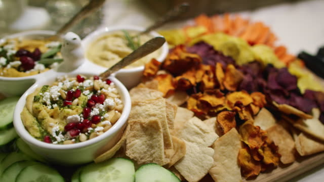 vídeos de stock e filmes b-roll de the camera pans around various dips, appetizers, fruits, cucumbers, beet crisps, crackers, and hummuses in bowls on a cutting board on a table at an indoor celebration/party - lanche