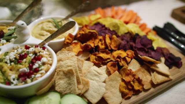 the camera pans around various dips, appetizers, fruits, cucumbers, beet crisps, crackers, and hummuses in bowls on a cutting board on a table at an indoor celebration/party - buffet stock videos & royalty-free footage