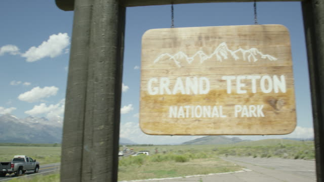 "the camera pans from cars and vehicles driving along a highway with the grand teton mountains in the background to the ""grand teton national park"" sign by the side of the road on a sunny day in western wyoming - grand teton stock videos & royalty-free footage"