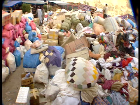 the camera pans over piles of supplies donated after an earthquake - bedclothes stock videos & royalty-free footage